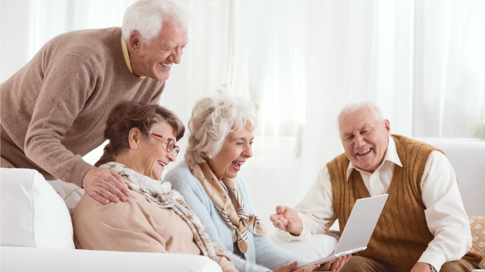 男女の老人がリビングに集まって楽しそうにしている