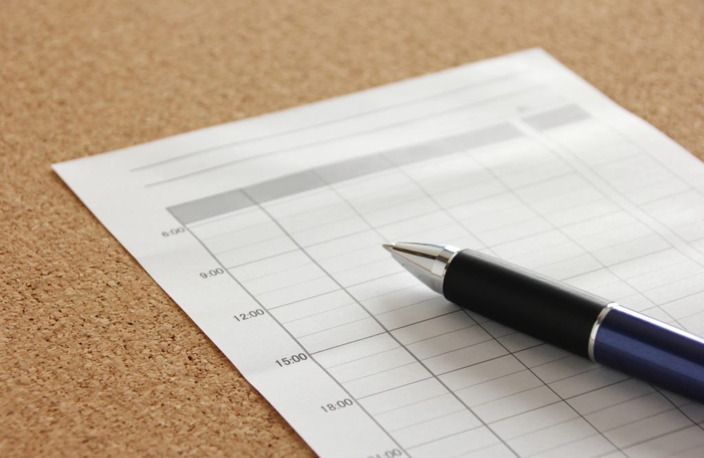 一日のタイムスケジュール表とその上に置かれたペン