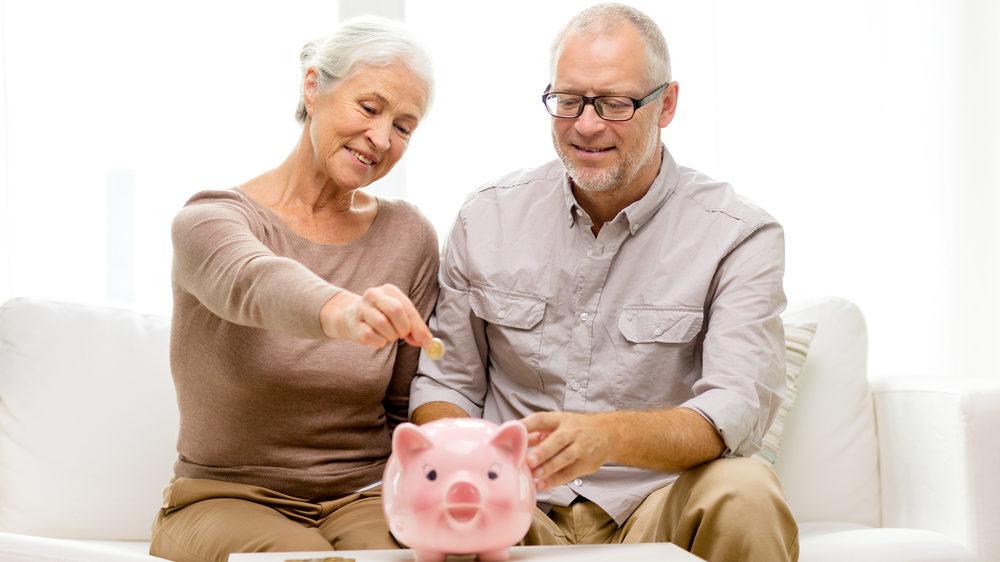 豚の貯金箱にお金を貯めている老夫婦