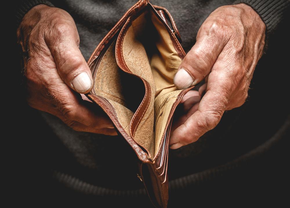 老人が空の財布を広げている画像