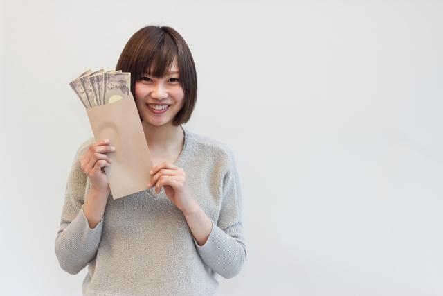現金を手に持つ笑顔の女性