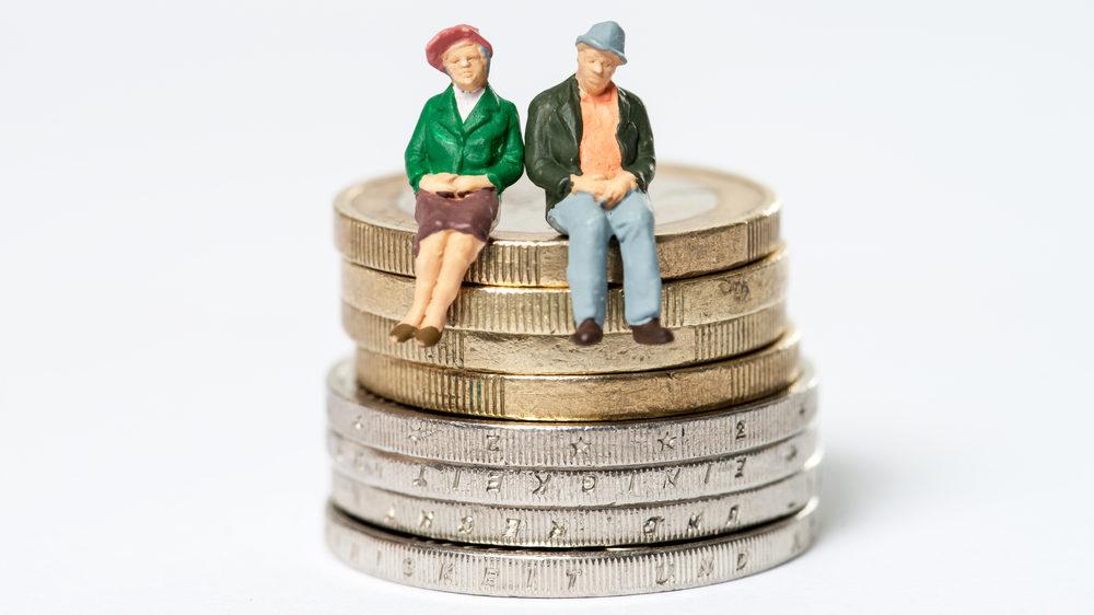 積み上げられたコインの上に腰掛ける老夫婦の人形