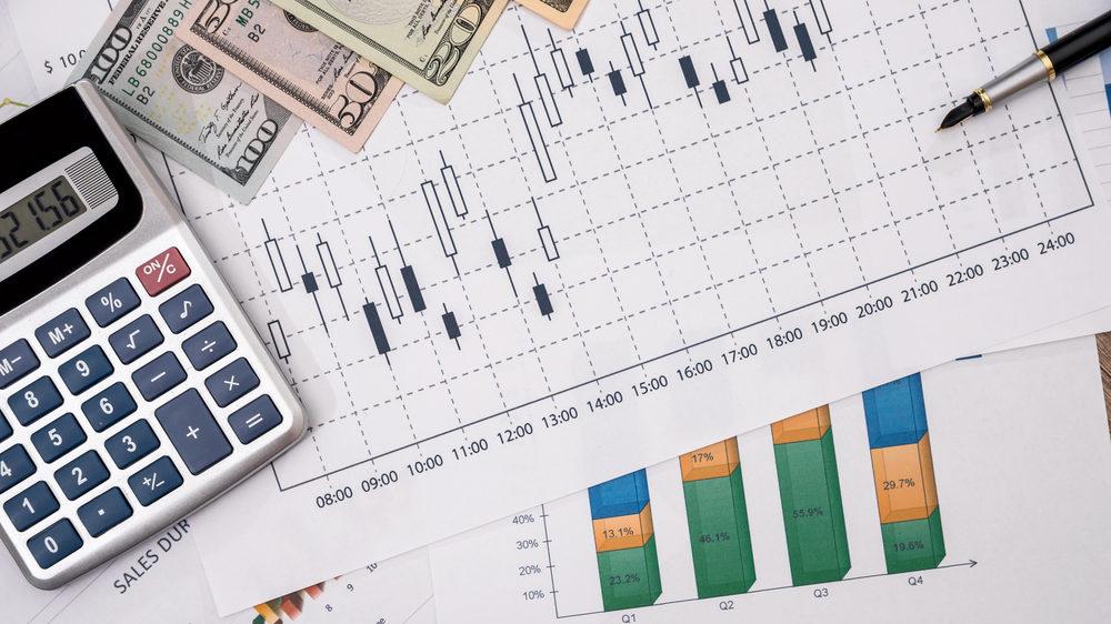 チャートが印刷された用紙の上に電卓とお札が置かれている画像