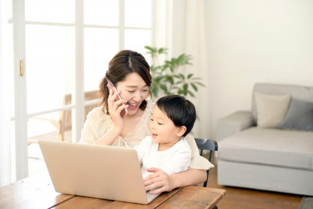 パソコン前に子供と座り電話をする女性