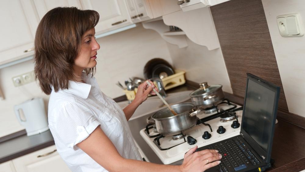 料理をしながらパソコンをチェックする女性