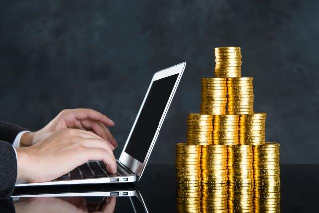 ノートパソコンと金貨