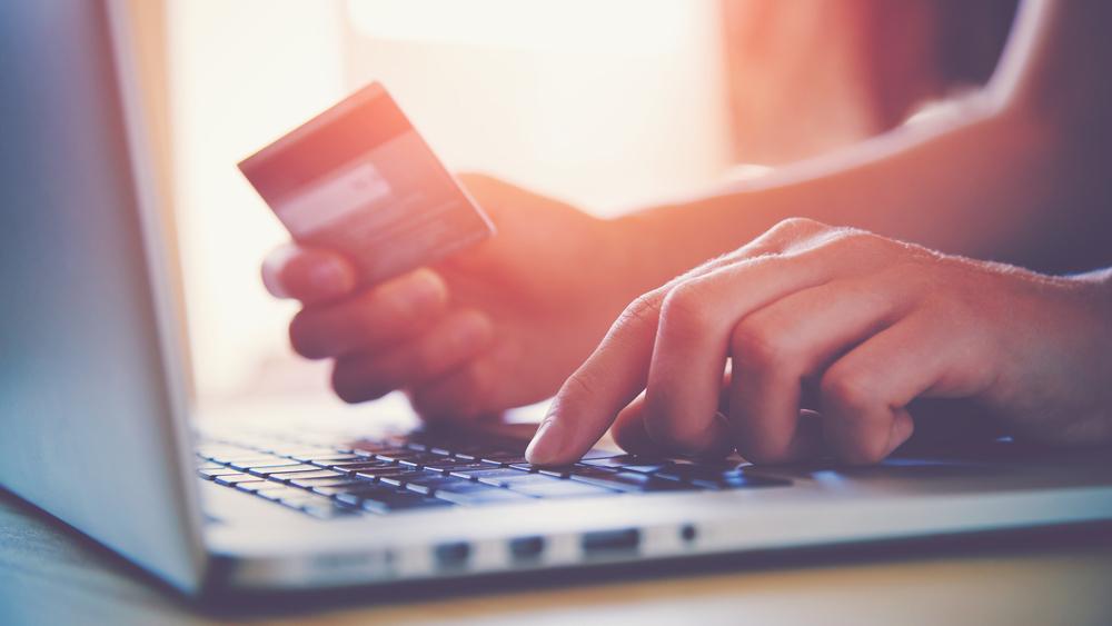 クレジットカード情報をパソコンで入力している女性