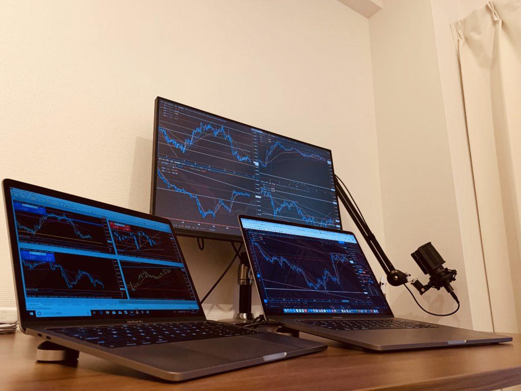 デスクの上に2台のノートパソコンと外付けモニターが置かれている