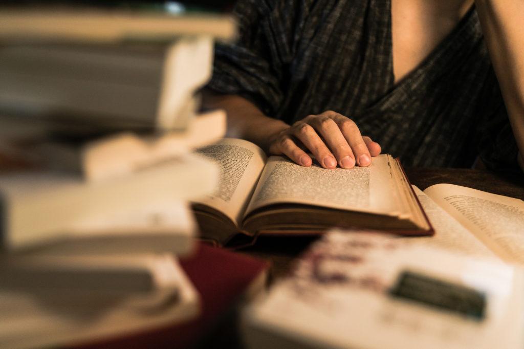 本をたくさん積み重ねて徹夜で調べ物をしている男性