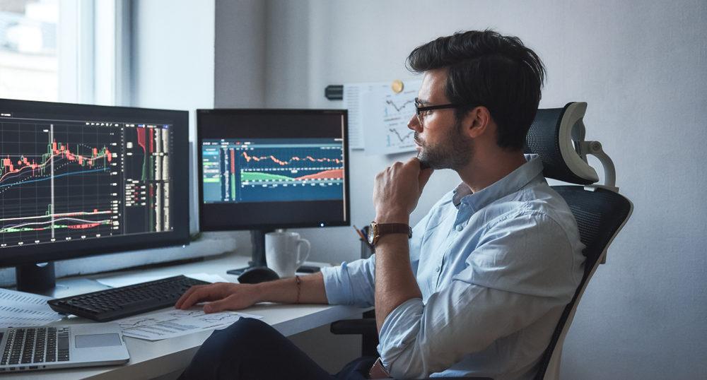 顎に指を当てて、デスク上のチャート画面を見ている男性