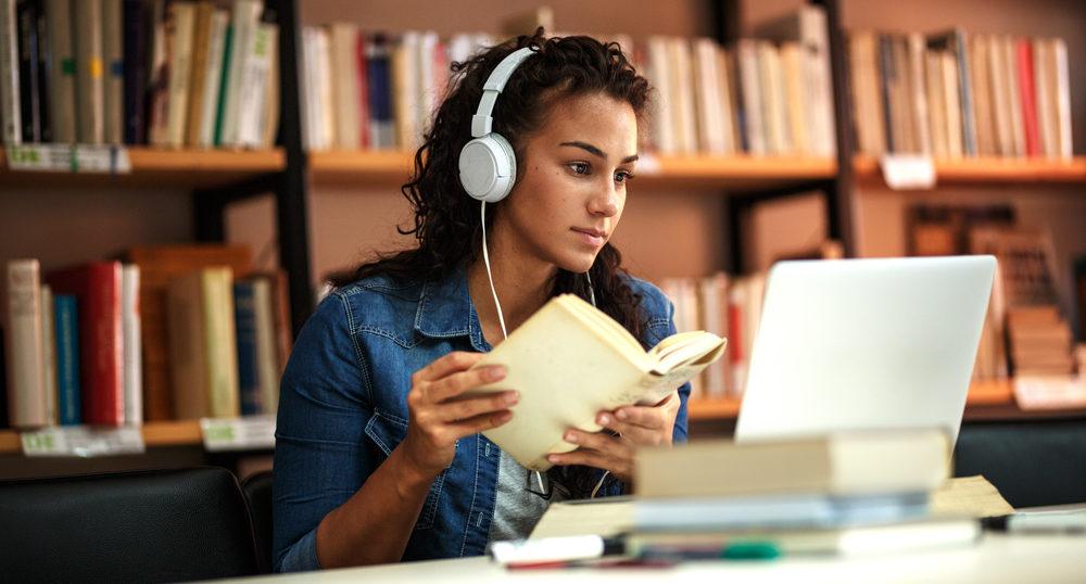 音楽を聴きながら図書館で勉強している女性
