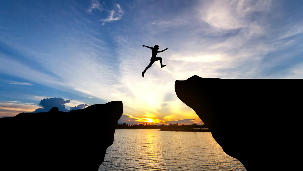 崖と崖の隙間をジャンプしている人