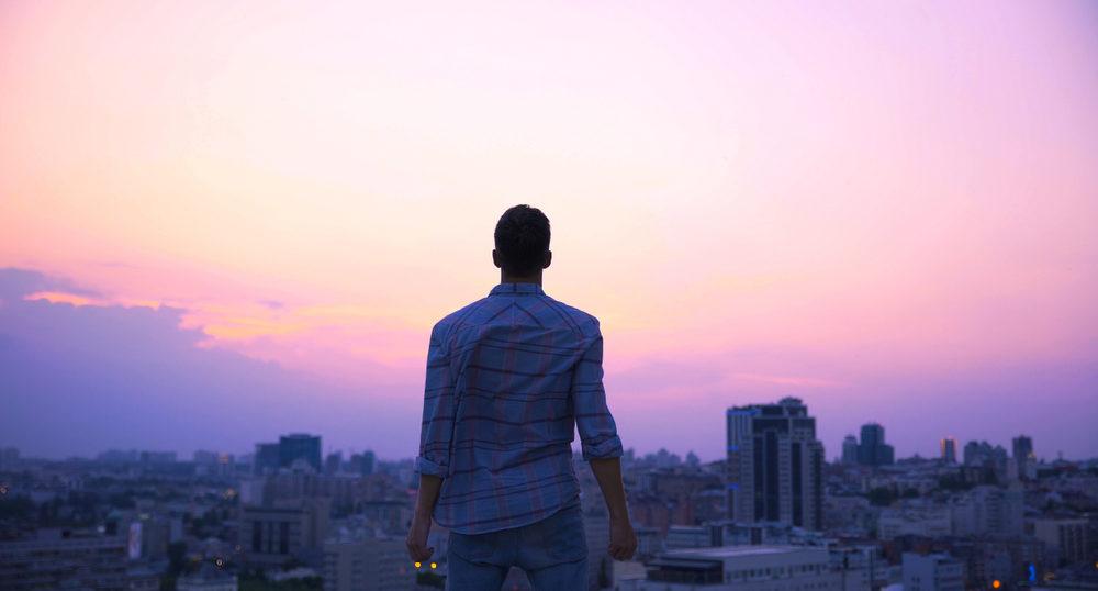 夕日の前に佇む男性